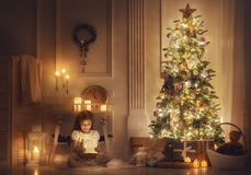 Girl with magic box. Merry Christmas and Happy Holidays! Cheerful cute little child girl with present. Kid holds a magic gift box near Christmas tree indoors Stock Photography