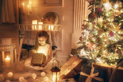 Girl with magic box. Merry Christmas and Happy Holidays! Cheerful cute little child girl with present. Kid holds a magic gift box near Christmas tree indoors Royalty Free Stock Photos