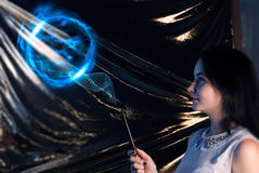 Girl with magic wand brunette-the sorcerer's apprentice, on a gold background, uses the spell. Happy Halloween stock photo