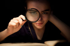 Girl with magnifir glass front eye Royalty Free Stock Photos