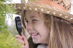 Girl with magnifying glass Stock Image