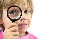 Girl with magnifying glass Stock Photos