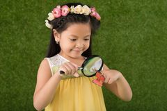 Girl with magnifying glass Stock Images