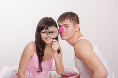 Girl with magnifying glass, guy clown nose Royalty Free Stock Photography