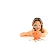 Girl with magnifying glass and piggy bank Royalty Free Stock Photo