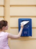 Girl and mail. Girl puts the letter into mailbox Royalty Free Stock Photography