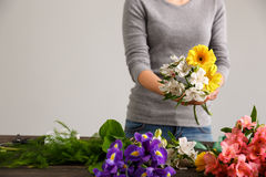 Girl make bouquet over gray background. Stock Photography