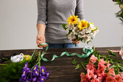 Girl make bouquet over gray background. Stock Photos
