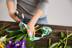 Girl  make a bouquet over gray background, cutting ribbon. Royalty Free Stock Photography
