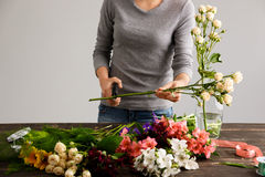 Girl  make a bouquet over gray background, cutting stem. Stock Photos