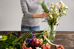 Girl make bouquet over gray background, putting flowers in vase. Royalty Free Stock Image