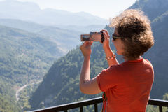 A girl make a photo on the camera a beautiful view Stock Image