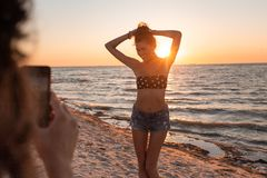 Girl make a photo of slim dark-haired girl in a swimsuit and shorts on the sandy beach near the sea on the sunset royalty free stock photo