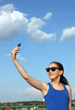 Girl make selfie on a smart phone Royalty Free Stock Image