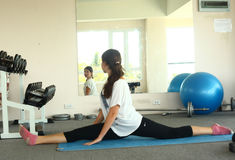 Girl make split in gym in front of the mirror Stock Images