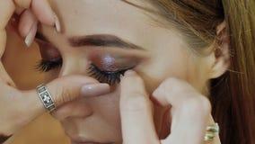 Girl make-up artist extends eyelash for model. Build-up. stock video