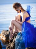 Girl with make-up in fantasy blue dress. Beautiful girl with make-up in blue fantasy dress sitting on the stone in water Stock Photo