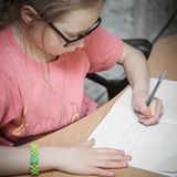 Girl make written lessons. Girl make written lessons at home royalty free stock images