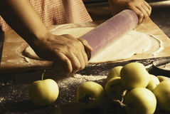 Girl makes an apple pie. Rolls the dough. Apples on the table.Toned, Vintage. Hands in picture royalty free stock image