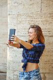 Girl makes a cheerful self-portrait on the phone outdoors. Selfi Stock Images