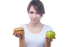 Girl makes choice between apple and hamburger Royalty Free Stock Images