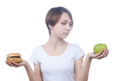 Girl makes choice between apple and hamburger Stock Images