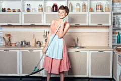 Girl makes cleaning the kitchen and sings. Royalty Free Stock Image