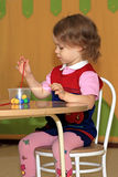 A girl makes a decoration. A little girl is engaged in making of decoration Royalty Free Stock Photography