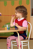 A girl makes a decoration. A little girl is engaged in making of decoration Royalty Free Stock Image