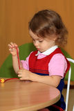A girl makes a decoration. A little girl is engaged in making of decoration Royalty Free Stock Images