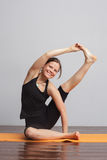 Girl makes a difficult asana of yoga kraunchasana. On the pendant is written yogic symbol Aum Stock Photos