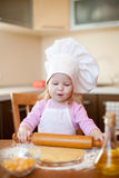 Girl makes dough on kitchen with rolling pin Royalty Free Stock Image