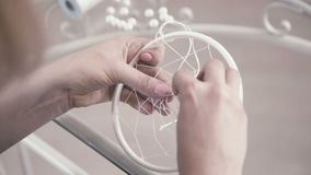 The girl makes Dreamcatcher - Hobbies Crafts. Dreamcatcher: the process of creating. Openwork weaving of white thread. The girl makes Dreamcatcher - Hobbies stock video footage