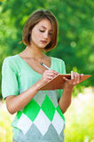 Girl makes an entry in notebook Stock Image
