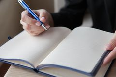 The girl makes entry in a notebook. close up stock image