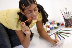 Girl makes fashion sketch. Beautiful girl watches fashion sketch wearing specs stock photo