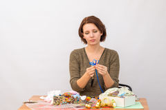 The girl makes a flower of decorative ribbons at the table with needlework Royalty Free Stock Photos
