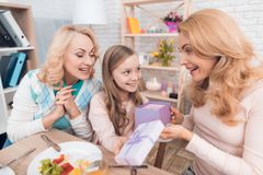 The girl makes a gift to mom and grandmother on March 8. They are sitting at the festive table stock photography