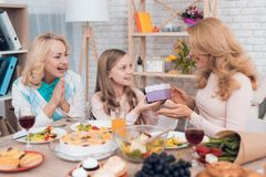 The girl makes a gift to mom and grandmother on March 8. They are sitting at the festive table royalty free stock images