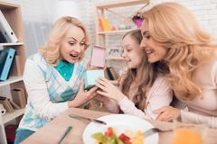 The girl makes a gift to mom and grandmother on March 8. They are sitting at the festive table royalty free stock photography