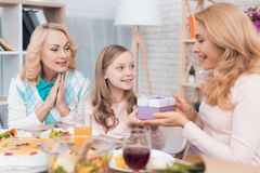 The girl makes a gift to mom and grandmother on March 8. They are sitting at the festive table stock photo