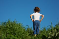 Girl makes gymnastic in grass, rear view Royalty Free Stock Images