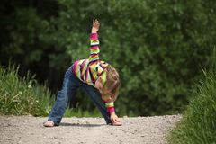 Girl makes gymnastic in park. Little girl makes gymnastic in park Royalty Free Stock Photos