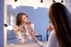 Girl makes herself makeup make-up in front of the mirror stock photos