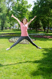 Girl makes a jump exercise outdoors Royalty Free Stock Photography