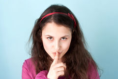 Girl makes keep a secret gesture Stock Photos