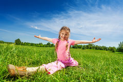Girl makes leg-split on grass with arms apart Royalty Free Stock Image