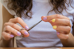 Girl makes a manicure with nail scissors. Girl in white t-shirt makes a manicure with nail scissors. Woman's hand with a bright purple-orange nail Polish Royalty Free Stock Photo