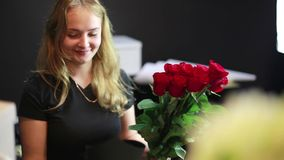 Girl makes packaging for roses in the flower shop. stock video footage