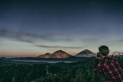 The girl makes a photo on the phone of the mountain volcano Batur on background night sky with stars Stock Photos